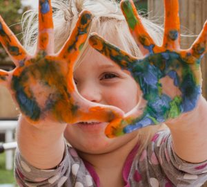 child with finger paint on hands