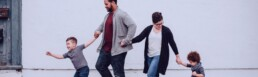 mother and father and two sons holding hands walking