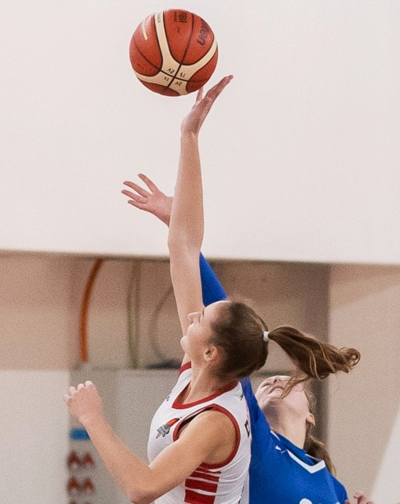 women reach for basketball
